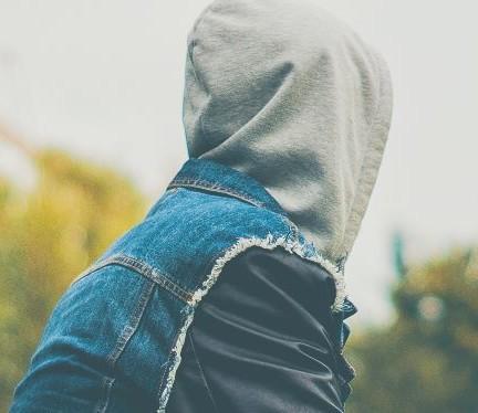 Huppupäinen nuorukainen istuu luonnossa ja katsoo poispäin kamerasta.